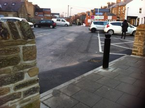 image of the wall and pedestrian entrance to car park with bollard in the middle of the path between the walls