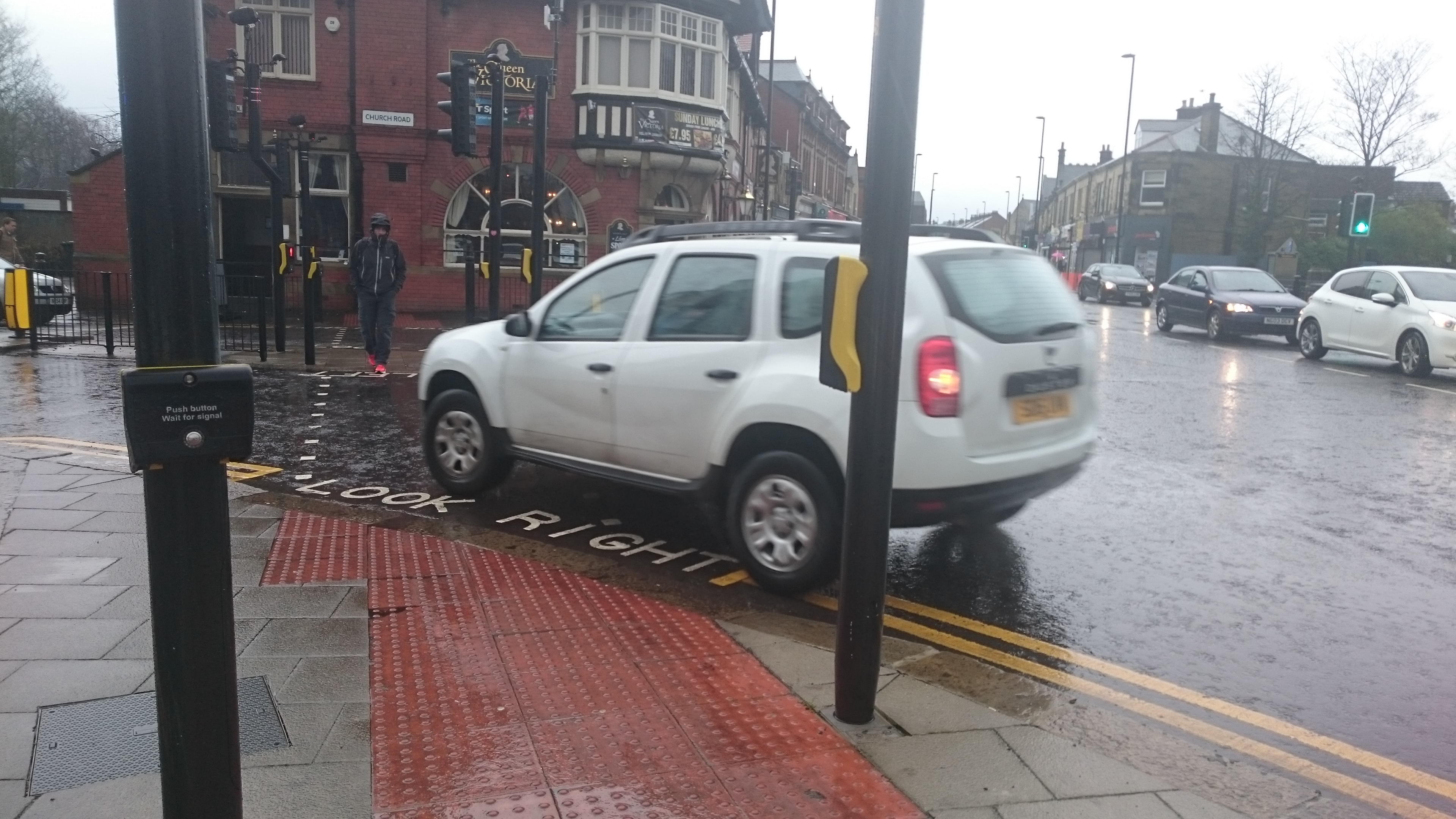 image of crossing across church road heading towards the Queen Victoria pub. Showing the tactile paving and the curved edge of the pavment. Look right is painted on the road. A car is turning across the crossing and is inches away from the pavement edge
