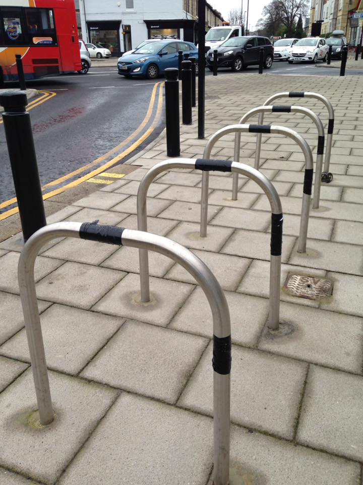 Five silver coloured bicycle racks outside of the gosforth hotel. Each bike rack has about eight inches of black tape wrapped around the middle of the top and front edges.