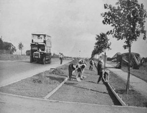This picture shows workmen with spades working on a new 1930s cycle track in London: to the left is a bus on the road - image courtesy of Carlton Reid