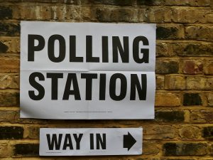 Image of a polling station sign on a brick wall with Way in sign underneath