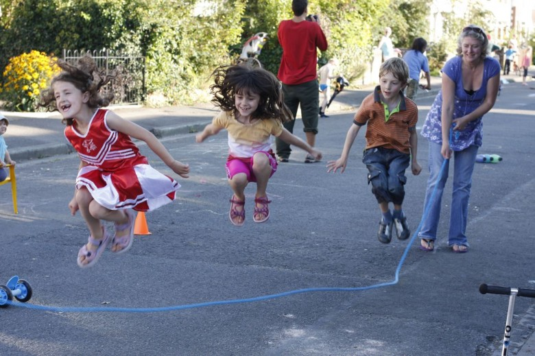 Three children jumping through a skipping rope in the street. Adults in the background.