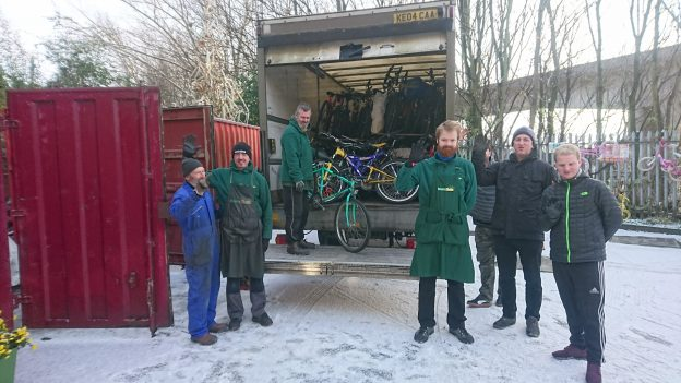 Asylum seekers with staff in front of a lorry with bikes