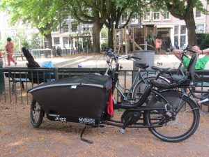 Electric cargo bike with child seat by a park in Amsterdam