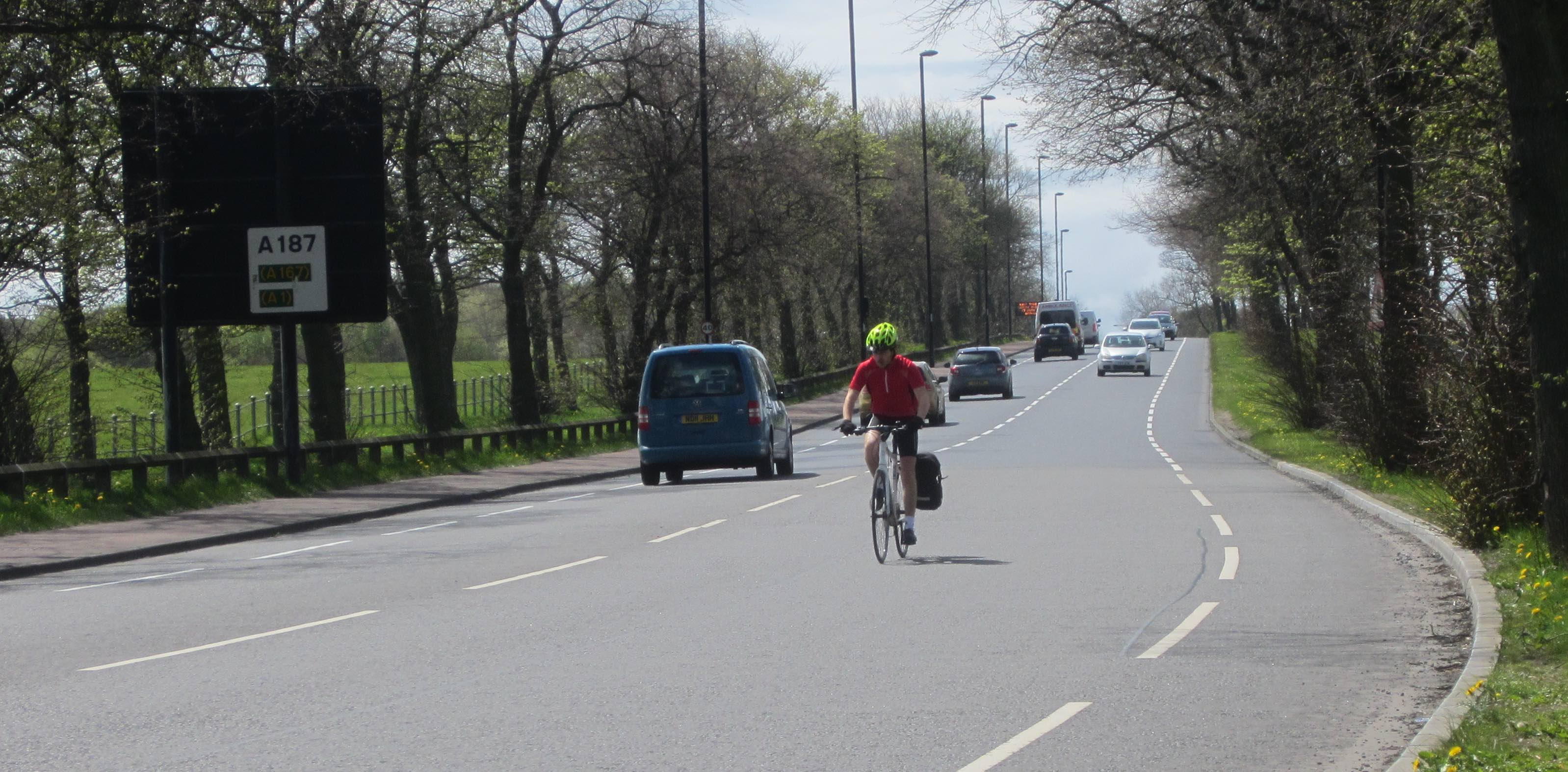 Person cycling in the main carriageway approaching the Kenton Road traffic lights.