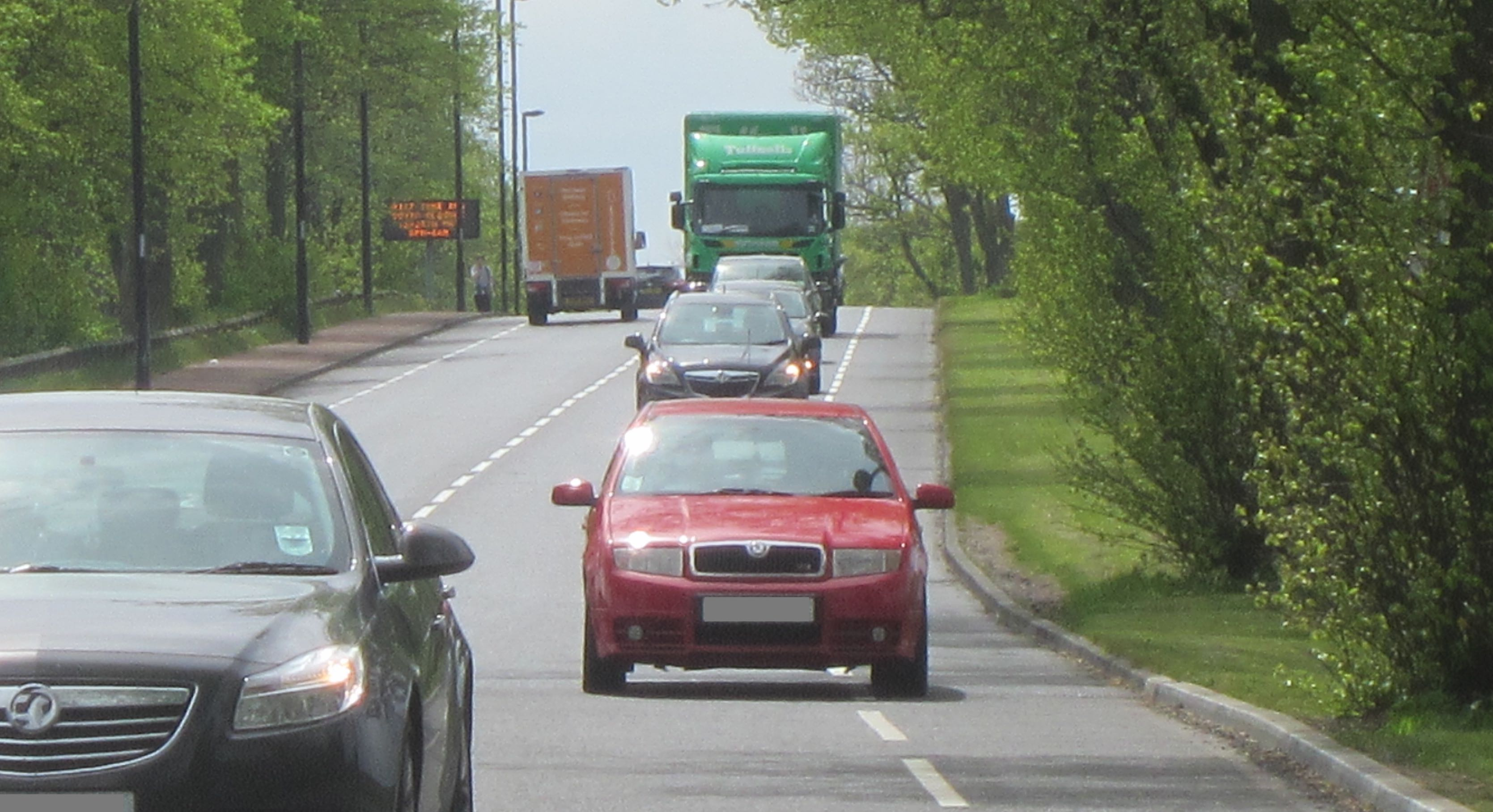 Red car driving in the cycle lane on Grandstand Road