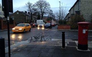 Photo of junction of Ivy Road with Salters Road. Vehicles are travelling up Salters with queued vehicles all the way back from the high street. In the foreground is a post box and pillar, with a deep puddle at the kerbside.