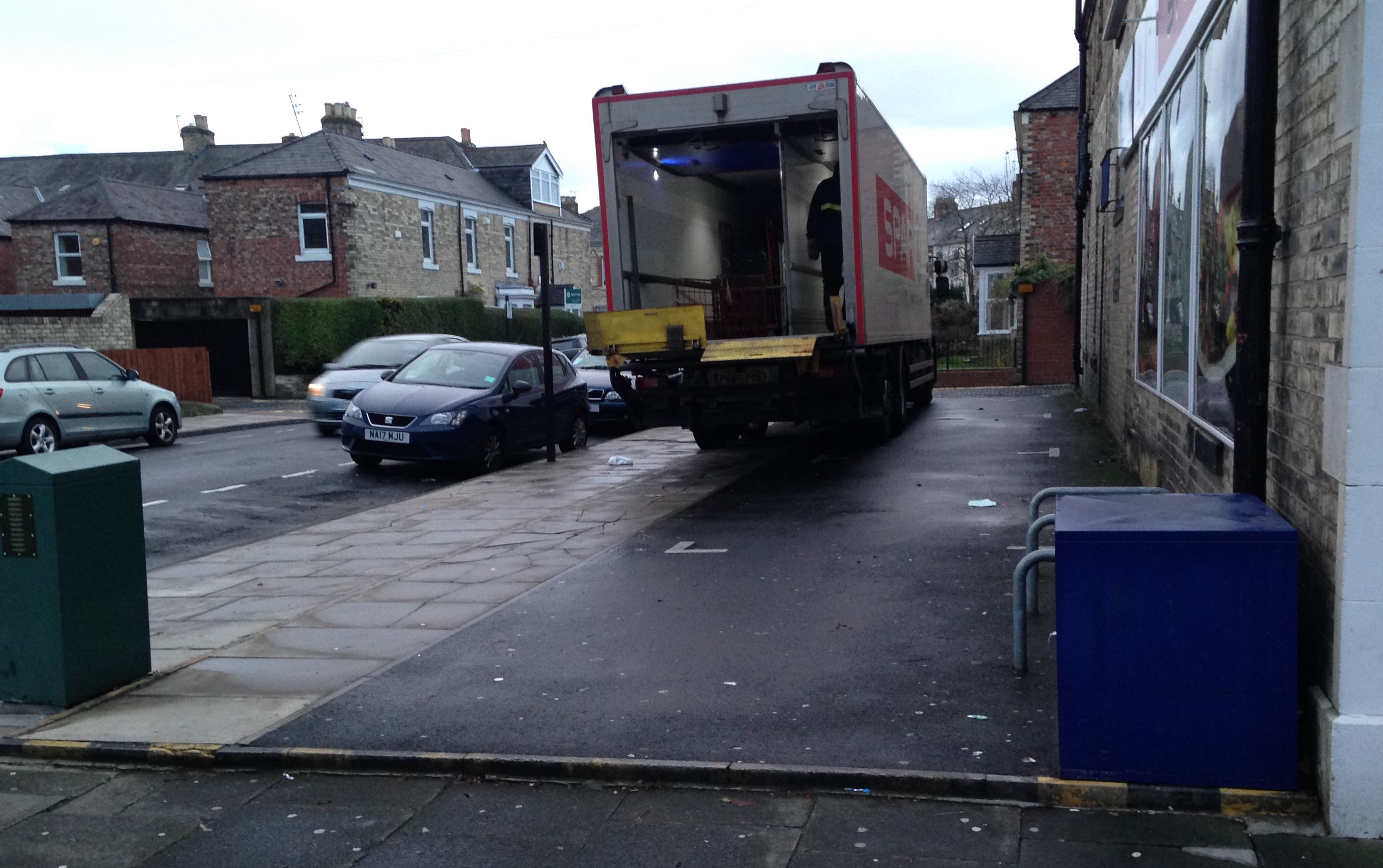 Delivery lorry parked on the parking space and pavement