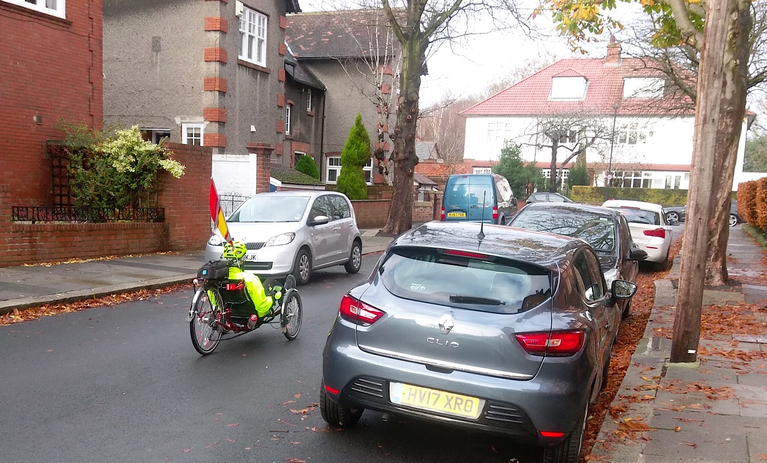 Photo of a recumbent cycle travelling between parked cars in West Gosforth.