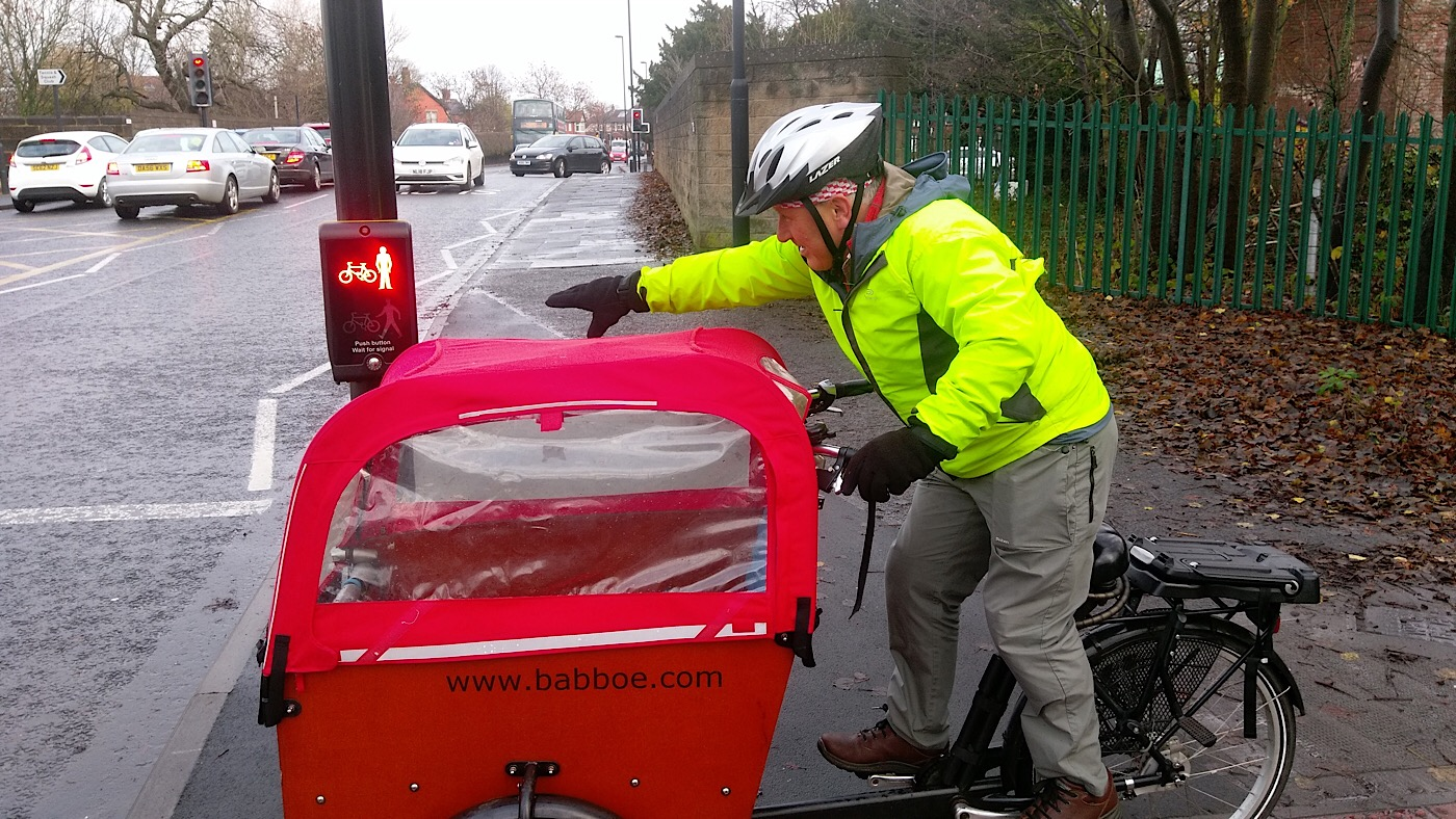 Picture of a cyclist with an adapted cycle trying to reach the button on a Pelican crossing.