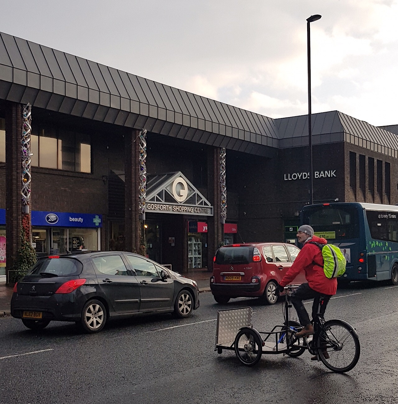 Picture of adapted cycle rider trying to cross traffic on Gosforth High Street.