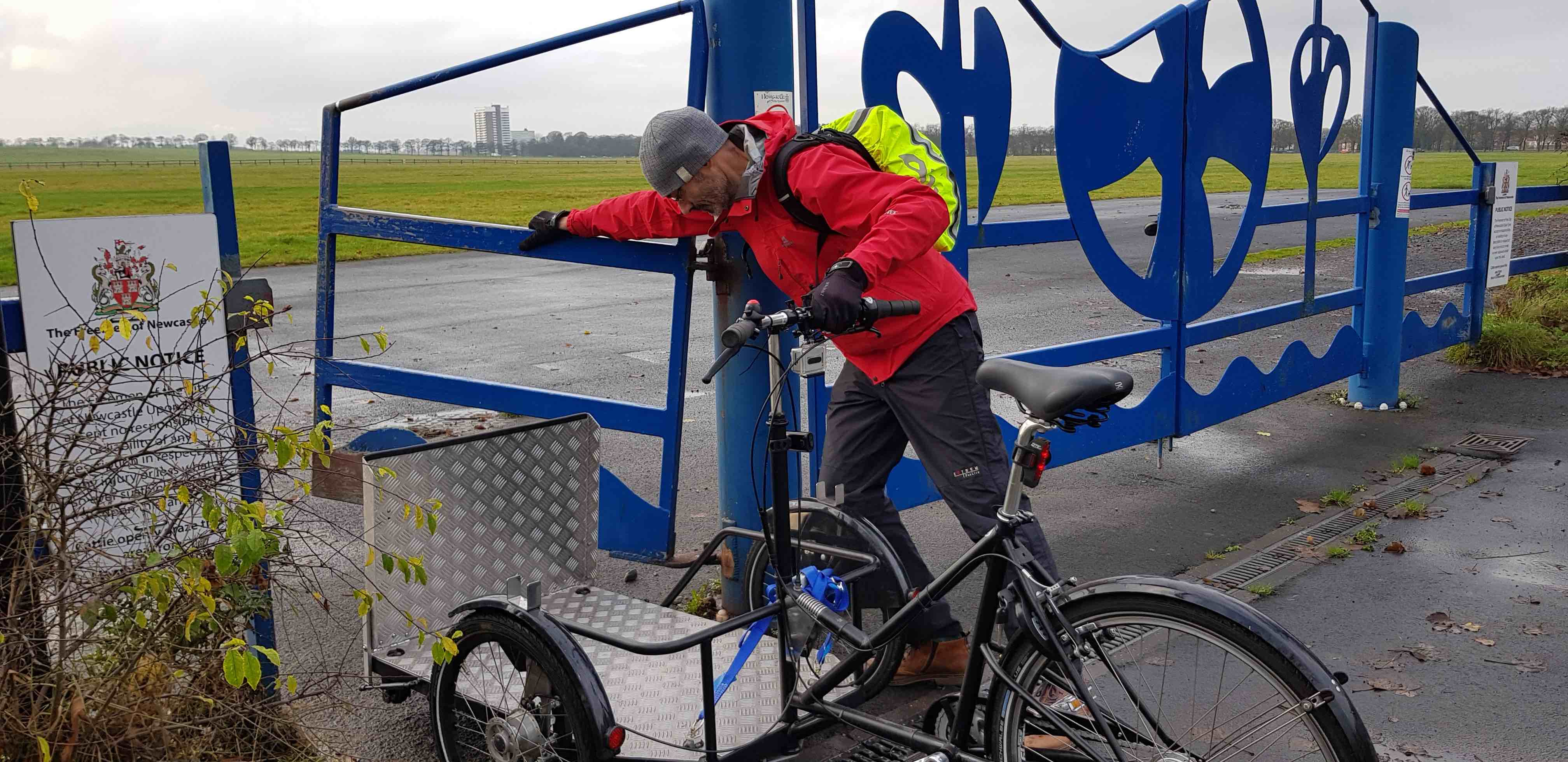 Picture of an adapted cycle rider struggling to open the gate to the Town Moor.