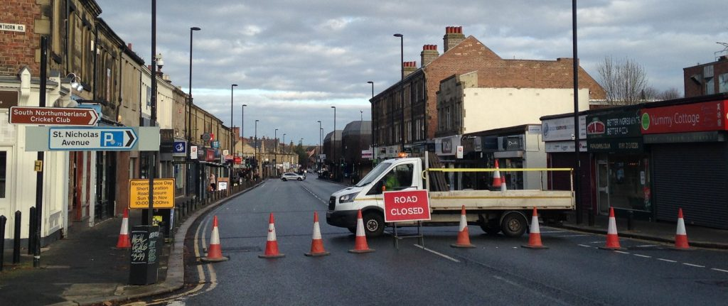 Picture of Gosforth High Street looking north from Hawthorn Road, with the road blocked by cones for the Remembrance Sunday parade.