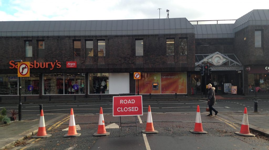 Picture of the junction of Ivy Road and the High Street, with cones across the end of Ivy Road.