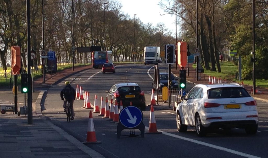 Picture of roadworks by Little Moor with cones and someone cycling inside the cones.