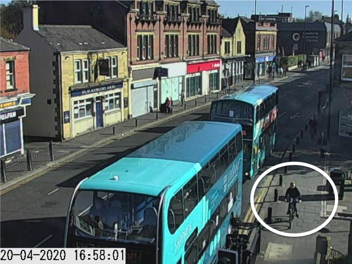 Traffic camera picture of Gosforth High Street with someone cycling on the pavement.