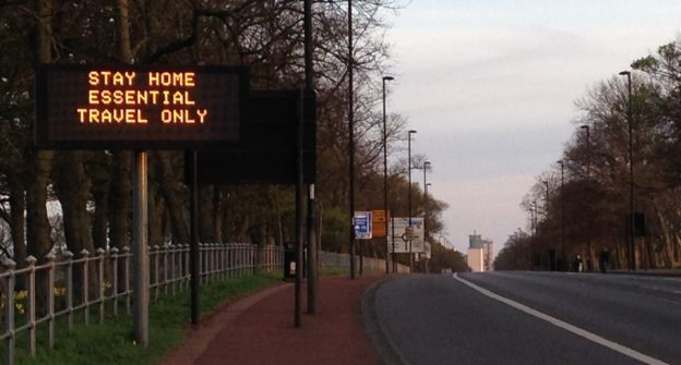 Electronic sign saying 'stay home essential travel only'