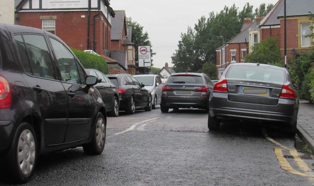Pircture of cars on Stoneyhurst Road in single file in between two rows of parked cars.