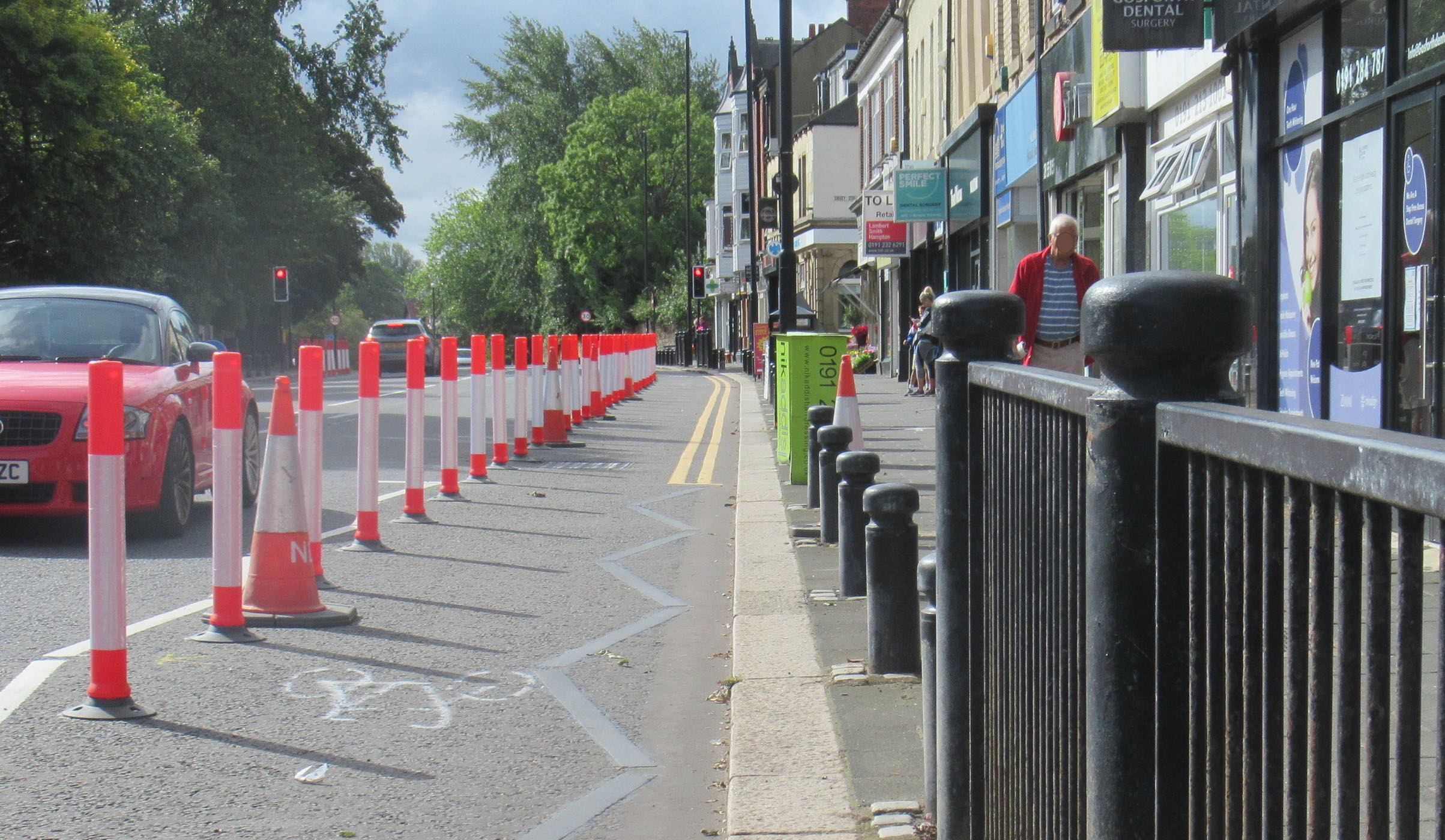 Cycle lane protected by poles west side of High Street south of The County