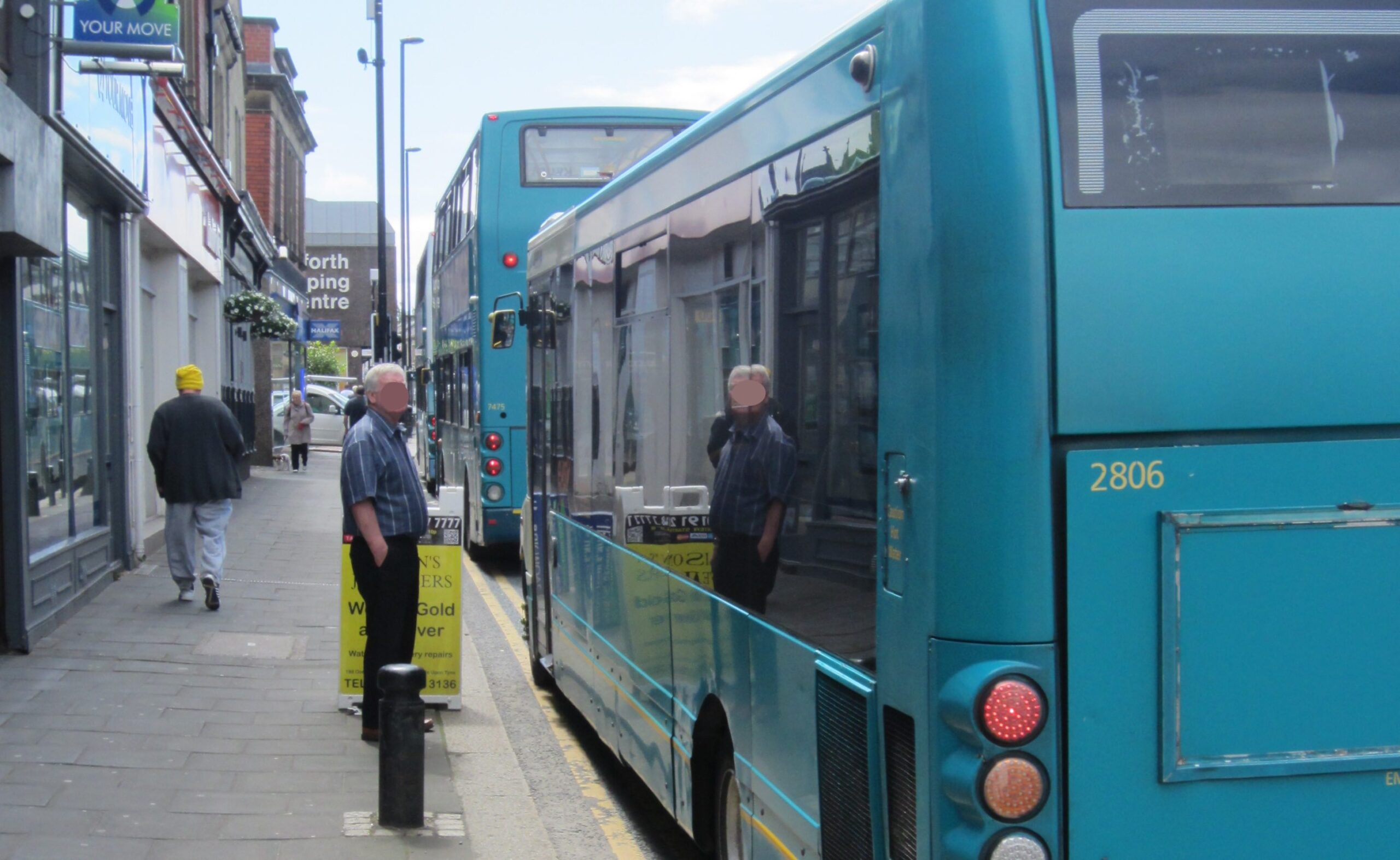 Man standing on the edge of the pavement on Gosforth High Street next to a bus.
